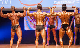 Male bodybuilders flexing muscles at championship on stage Stock Images