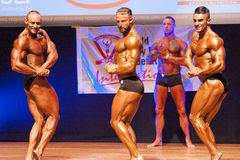 Male bodybuilders flexing muscles at championship on stage Royalty Free Stock Images