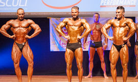 Male bodybuilders flexing muscles at championship on stage Royalty Free Stock Photos