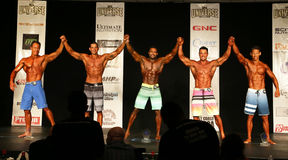 Male Bodybuilders Raise Arms in Victory. The top 5 link arms in victory for the 35 & Over Class in the Men's Physique finals of the 2016 NPC Universe held Stock Photo