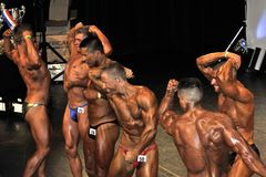 Male bodybuilding contestant showing his best. ROOSENDAAL, THE NETHERLANDS - OCTOBER 19, 2014. Male bodybuilders in a line up at the bodybuilding and fitness Royalty Free Stock Images