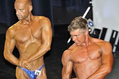 Male bodybuilding contestant showing his best. ROOSENDAAL, THE NETHERLANDS - OCTOBER 19, 2014. Male bodybuilders showing their best at the bodybuilding and Royalty Free Stock Image