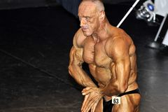 Male bodybuilding contestant showing his best. ROOSENDAAL, THE NETHERLANDS - OCTOBER 19, 2014. Male bodybuilders showing their best at the bodybuilding and Stock Image