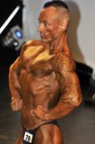 Male bodybuilding contestant showing his chest pose. ROOSENDAAL, THE NETHERLANDS - OCTOBER 19, 2014. Male bodybuilders showing their best at the bodybuilding and Royalty Free Stock Photo