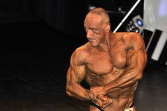 Male bodybuilding contestant showing his chest pose. ROOSENDAAL, THE NETHERLANDS - OCTOBER 19, 2014. Male bodybuilders showing their best at the bodybuilding and Stock Photo