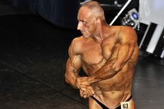 Male bodybuilding contestant showing his chest pose. ROOSENDAAL, THE NETHERLANDS - OCTOBER 19, 2014. Male bodybuilders showing their best at the bodybuilding and Royalty Free Stock Photos