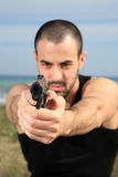 Male bodyguard with a gun. Young male bodyguard holding a gun selective focus stock image