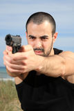 Male bodyguard with a gun. Young male bodyguard holding a gun selective focus stock images