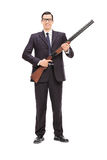 Male bodyguard holding a shotgun. Full length portrait of a male bodyguard holding a shotgun isolated on white background royalty free stock photo