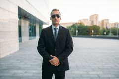 Male bodyguard in suit, earpiece and sunglasses royalty free stock image