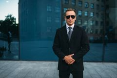 Male bodyguard in suit, earpiece and sunglasses royalty free stock images