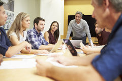 Male Boss Addressing Meeting Around Boardroom Tabl. E In Architect Office Stock Photos