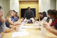 Male Boss Addressing Meeting Around Boardroom Table stock photos