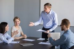 Male boss congratulating female employee with good results at me. Millennial businessman talking to female worker during company briefing, complimenting for good stock photo