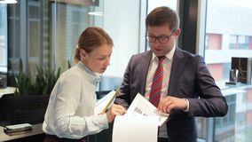 A male boss is discussing economical report with the female analytic in the modern office. He is holding the report in his hands, turning over its pages and stock video