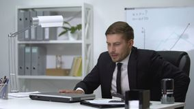 Male boss finishing work on laptop, standing up and feeling strong pain in back stock video