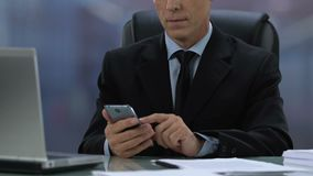 Male boss in formal suit checking meeting calendar in smartphone, business app