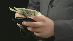 Male boss getting money out of his wallet, counting and putting back. Rich man stock video footage