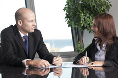Male boss with his secretary. Businessman with his secretary in a stylish office with harbor in the background Stock Photo