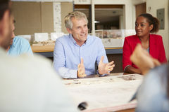 Male Boss Leading Meeting Of Architects Sitting At Table. Having A Discussion Royalty Free Stock Photo