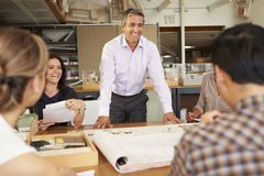 Male Boss Leading Meeting Of Architects Sitting At Table Royalty Free Stock Photography
