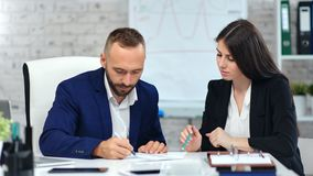 Male boss making signature on paper contract agreement using pen looking on data at workplace. Medium shot. Focused employee businesswoman and businessman in stock footage