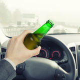 Male with bottle of beer while driving car - 1 to 1 ratio. Male holding bottle of beer while driving car - 1 to 1 ratio Royalty Free Stock Photography