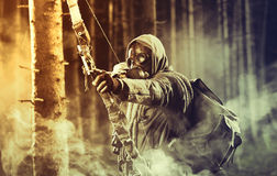 A male bow hunter wearing gas mask. Draws back on his bow Royalty Free Stock Image