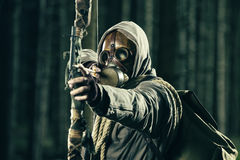 A male bow hunter wearing gas mask. Draws back on his bow Royalty Free Stock Photos
