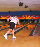 Male bowler in action. Senior male bowler on the alley in action completing his delivery Royalty Free Stock Images