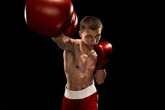 Male boxer boxing with dramatic edgy lighting in a dark studio Stock Image
