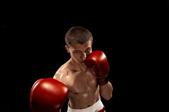 Male boxer boxing with dramatic edgy lighting in a dark studio Stock Photos