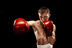 Male boxer boxing with dramatic edgy lighting in a dark studio Royalty Free Stock Photo
