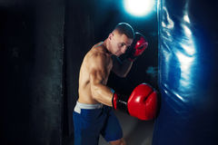 Male boxer boxing in punching bag with dramatic edgy lighting in a dark studio Stock Photo