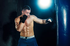 Male boxer boxing in punching bag with dramatic edgy lighting in a dark studio Royalty Free Stock Images