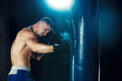 Male boxer boxing in punching bag with dramatic edgy lighting in a dark studio Stock Photography