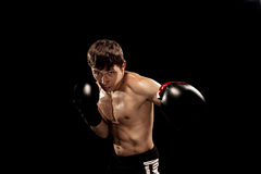 Male boxer boxing in punching bag with dramatic edgy lighting in a dark studio Stock Images