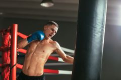 Male boxer hitting punching bag at a boxing studio. Sport training concept stock image