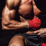 Male boxer with perfect body preparing for the fight and training wearing gloves. Royalty Free Stock Image