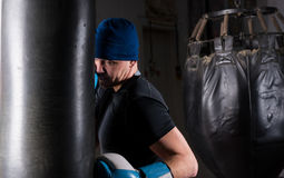Male boxer with stern look in a hat and boxing gloves training w. Ith boxing punching bag in a gym Stock Photos