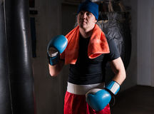Male boxer with a towel around his neck in a hat and boxing glov. Es after training with boxing punching bag in a gym Royalty Free Stock Image