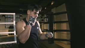 Male boxer training in boxing club. He furiously punching a bag stock footage