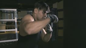 Male boxer training in boxing club. He furiously punching a bag. Slow motion stock footage