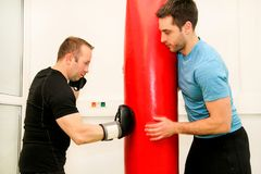 The male boxer training at gym. Athletic men punching her male partner and instructor with red boxing gloves at gym club. Attractive sports men is practicing Stock Photos
