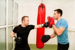 The male boxer training at gym. Athletic men punching her male partner and instructor with red boxing gloves at gym club. Attractive sports men is practicing Royalty Free Stock Photography