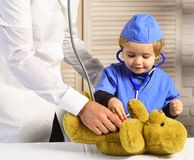 Male and boys hands hold stethoscopes on wooden background. Father and kid with interested face playing doctor. Healthcare and childhood concept. Pediatrician Stock Photography