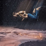 The male break dancer in water. The fantasy image of male break dancer in water on dark sky background Flying over the city at night Stock Photography