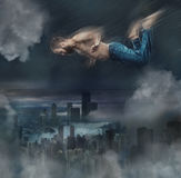 The male break dancer in water. The fantasy image of male break dancer in water on dark sky background Flying over the city at night Stock Photo