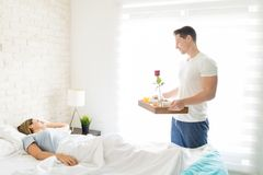 Male With Breakfast Tray Looking At Female Sleeping In Bed. Happy male carrying breakfast tray while looking at female sleeping in bed at home Stock Image