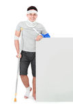 Male with broken arm and crutch presenting Stock Photo